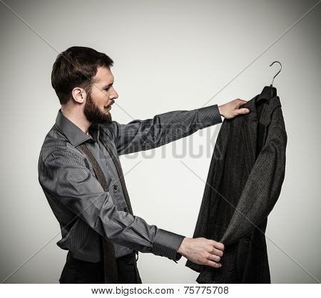 Handsome man with beard choosing jacket