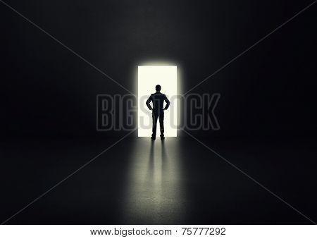 back view of businessman before the open door in a dark room