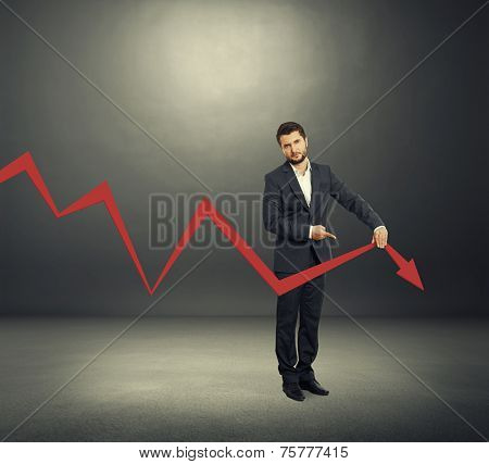 sad broker holding and pointing at falling down graph. photo in the dark room
