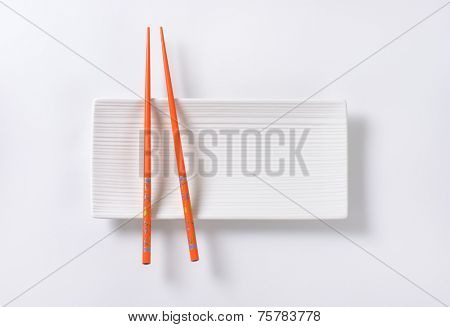 pair of orange chopsticks on white plate