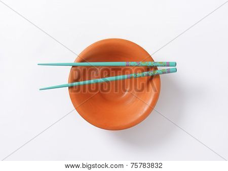 pair of blue chopsticks and empty orange bowl on white background