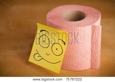 Drawn smiley face on a post-it note sticked on a toilet paper roll