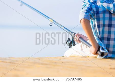 Close-up of hands of a boy with a fishing rod that is fishing on the pier