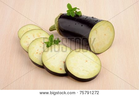 Sliced Aubergine, Eggplant With Mint Leaves On Bright Wooden Table