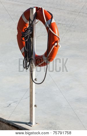 life preserver and rope on a white column