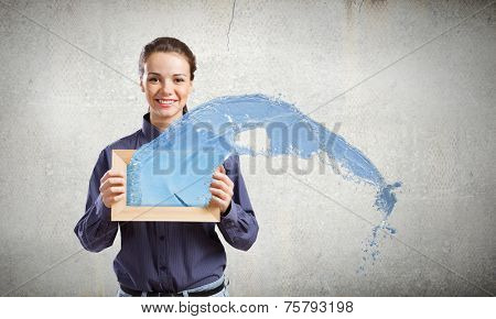 Young woman in shirt with wooden frame in hands