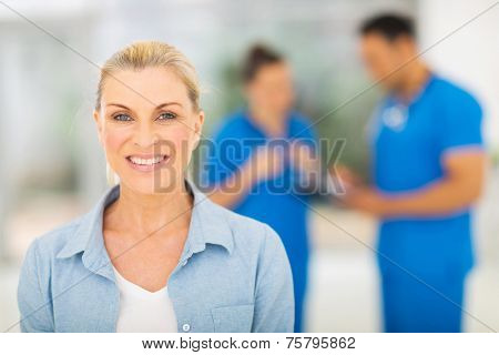 smiling middle aged woman waiting for checkup in doctor's office