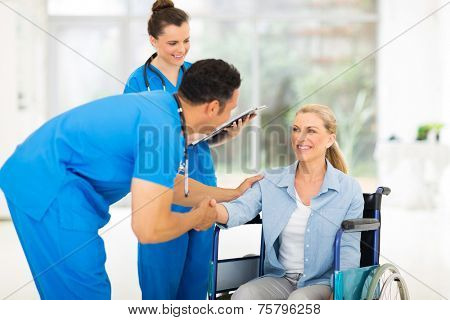 caring male doctor greeting handicapped patient