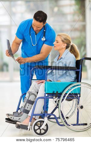 doctor explaining x-ray results to patient in wheelchair