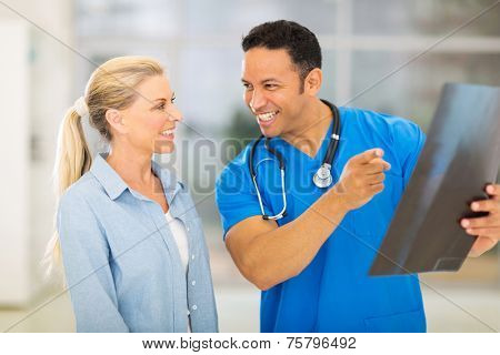 happy doctor and senior patient looking at x-ray result in hospital