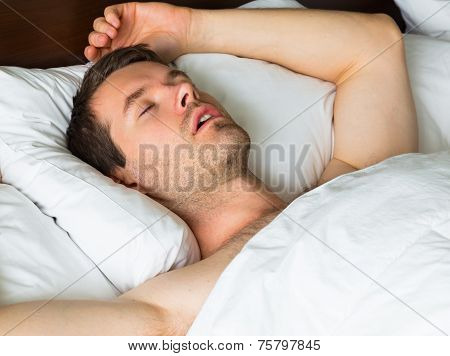 Sleeping man in bed with his arm up