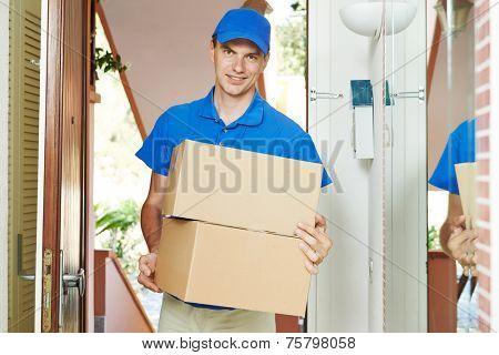 Smiling male postal delivery courier man indoors delivering parcel package boxes