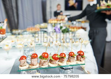 Waiter with meat dish serving catering table with food snacks