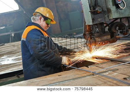 adult industrial worker at spot welding machine in factory workshop