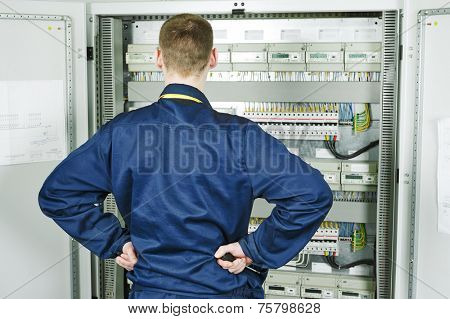 electrician builder engineer standing in front of opened fuseboard