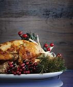 foto of roast chicken  - Scrumptious roast turkey chicken on platter with festive decorations for Thanksgiving or Christmas lunch against dark recycled wood background - JPG