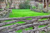 stock photo of log fence  - Old Split Log Fence in a Decorative garden - JPG