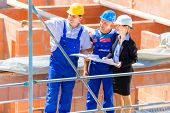 picture of real-estate-team  - Construction site Team or architect and builder or worker with helmets discuss on a scaffold construction plan or blueprint or checklist  - JPG