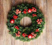 stock photo of mistletoe  - Christmas decorative wreath with leafs of mistletoe on wooden background - JPG