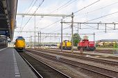 pic of passenger train  - Yellow passenger train leaving the platform of a train station