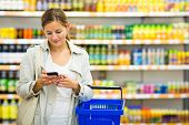 picture of grocery store  - Pretty young woman buying groceries in a supermarket - JPG