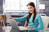 picture of single woman  - Happy young woman using laptop computer at home - JPG