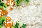 stock photo of ginger bread  - ginger biscuits and a branches of a Christmas tree on a white wood background - JPG