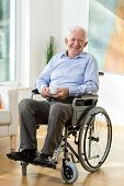 stock photo of older men  - Older smiling man on wheelchair with cup of hot coffee - JPG