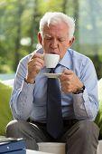 picture of older men  - Photo of elegant older man drinking hot coffee in his office - JPG
