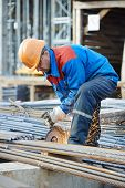 foto of construction machine  - Construction builder worker with grinder machine cutting metal reinforcement rebar rods at building site - JPG