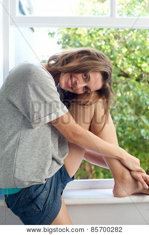 Pretty Mid Adult Woman Smiling By Window At Home