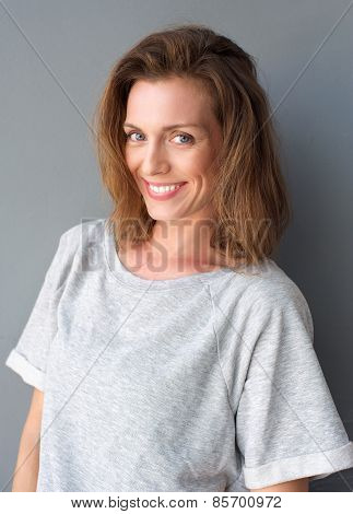 Portrait Of A Beautiful Mid Adult Woman Smiling On Gray Background