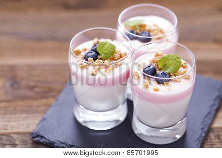 Delicious Dessert, Flakes Flooded In Two Flavors Yogurt With Blueberries And Fruit On A Wooden Board