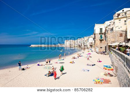 CEFALU,SICILY-SEP 16,2014: Unidentified people on sandy beach in Cefalu, Sicily, Italy at Sep 16, 2014. Cefalu is an attractive historic town and seaside resort.