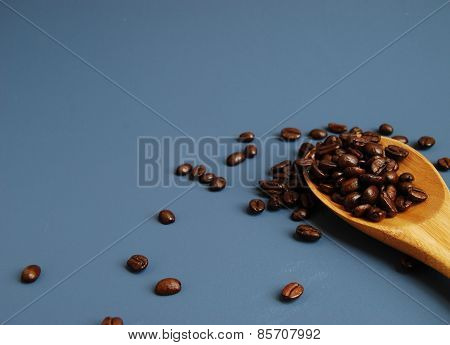 Arabica Coffee Beans in a Bamboo Spoon, Scattered Against a Blue Background