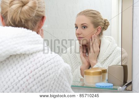 Young Beautiful Woman Looking At Mirror In Bathroom