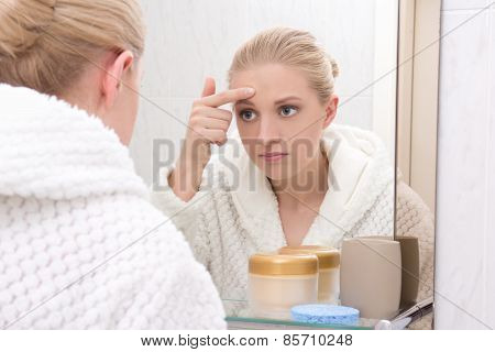 Beautiful Woman With Problem Skin Looking At Mirror In Bathroom