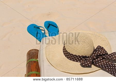 Straw hat and flip flops on sand beach