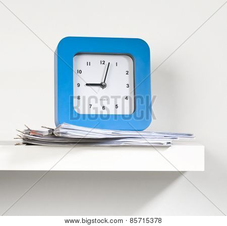 Big clock placed on a few paper documents on the white shelf.