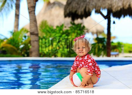 cute toddler girl playing with ball in swimming pool