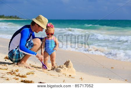 father and little daughter playing with sand on the beach