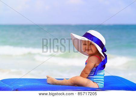 cute little girl in big hat on summer beach