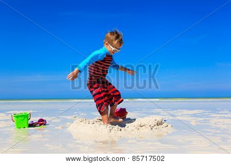 little boy jumping on tropical beach