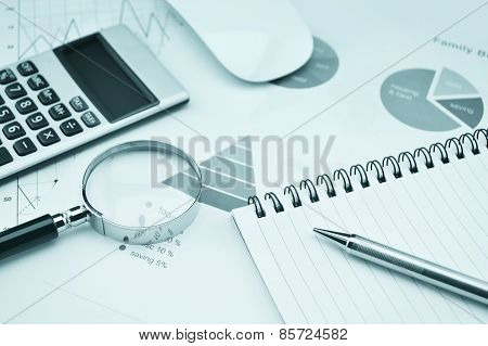 Book, Magnifying Glass, Pen And Calculator On Financial Chart And Graph