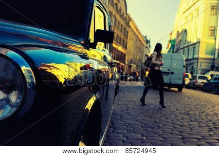 Girl Crossing The Road Of Stones Between The Cars In The City