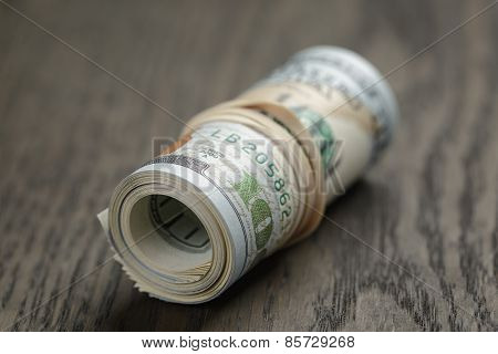 roll of hundred dollar bills on wooden table