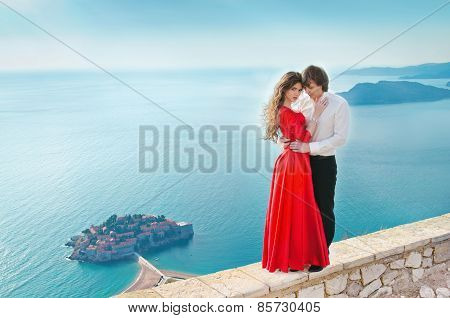 Romantic Young Couple In Love Over Sea Shore Background. Fashion Girl Model In Red Dress With Handso