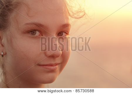 Portrait of a beautiful teen girl in the sunset on the sea