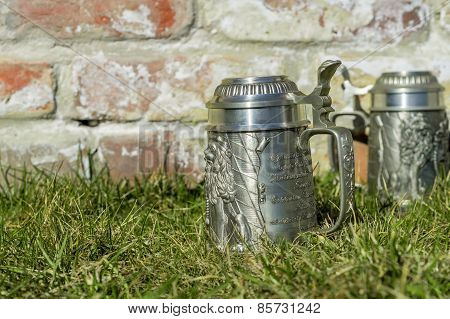 Two Beer Mugs On The Grass Near The Brick Wall