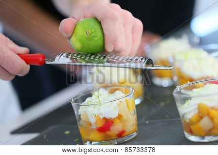 Cook rubbing lemon zest with grater over dessert